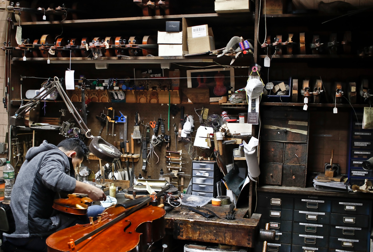 The shop is full of hundreds of tools used to restore instruments. Rigoberto Dubon worked to repair a violin.