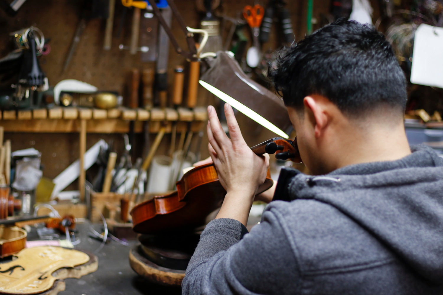 After truing the fingerboard Rigoberto Dubon added the strings back to the violin.