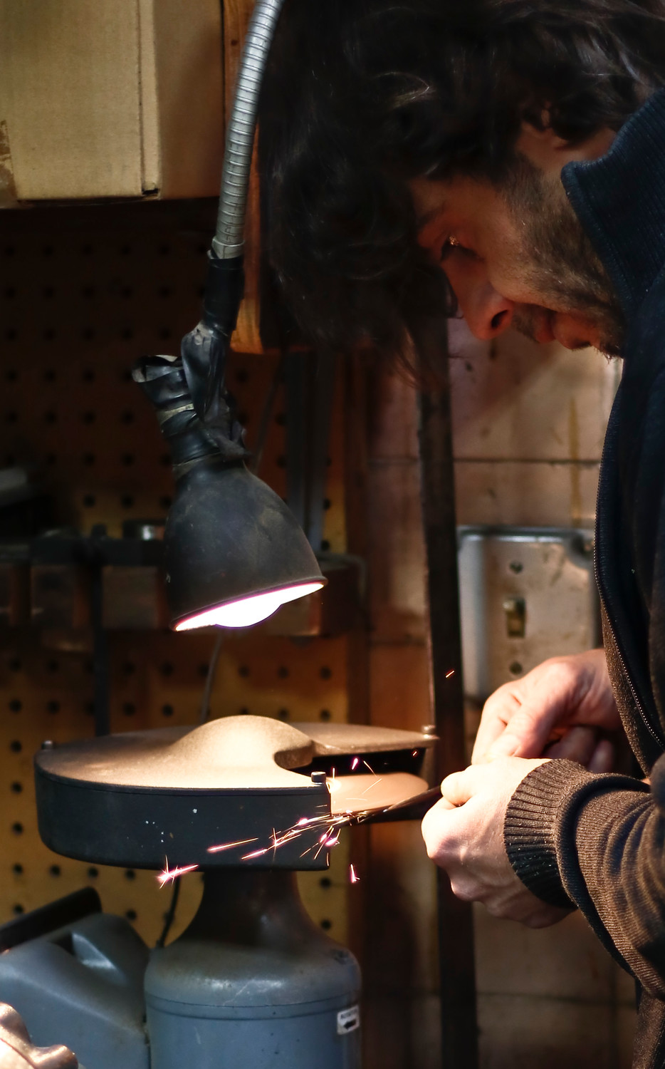 Simone Diana hones the chisel he is using to carve the edges of a new bass.