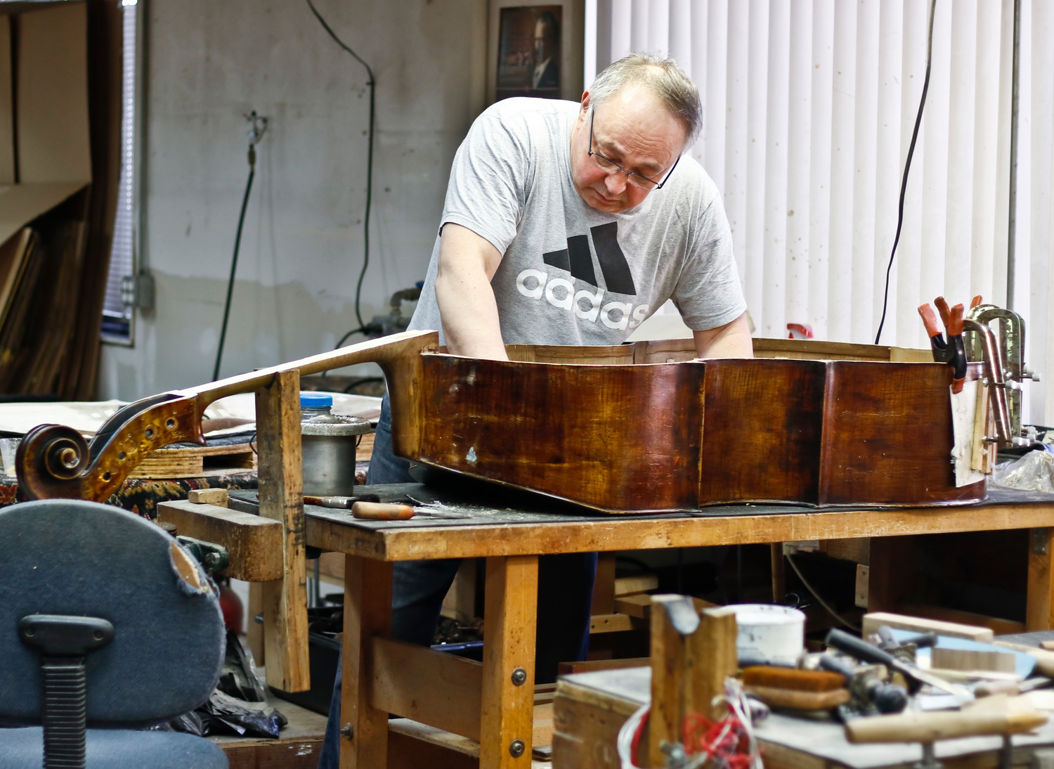 Andy Nerkowski works on the restoration of an older bass.