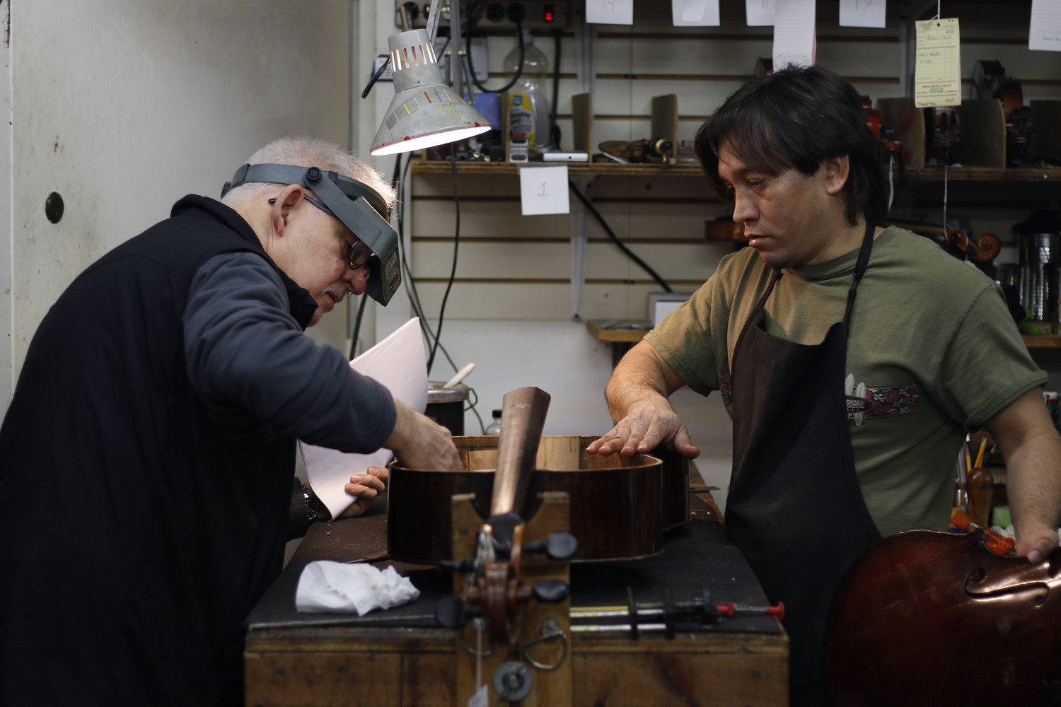 Jake Cradilas and Ricardo Hernandez make a final examination of the repairs before gluing the cello back together.