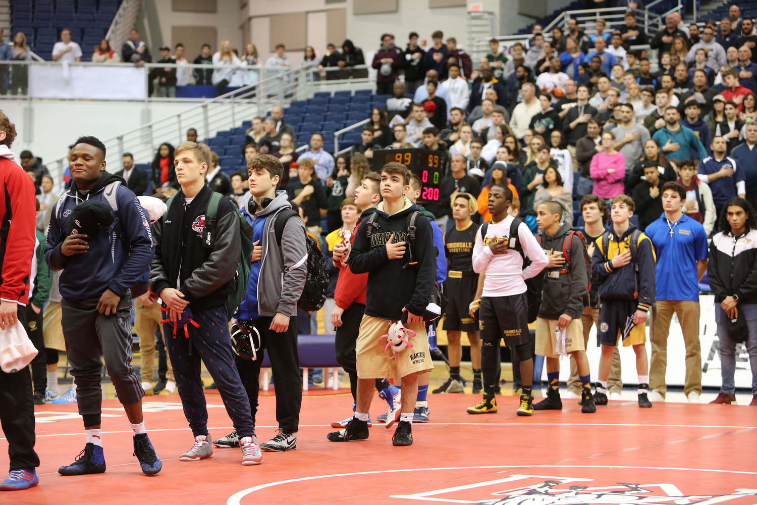 Vines, center, stood at attention for the flag with his fellow competitors. He, along with four of his teammates, would come back to the mat later in the night to win an individual county title.