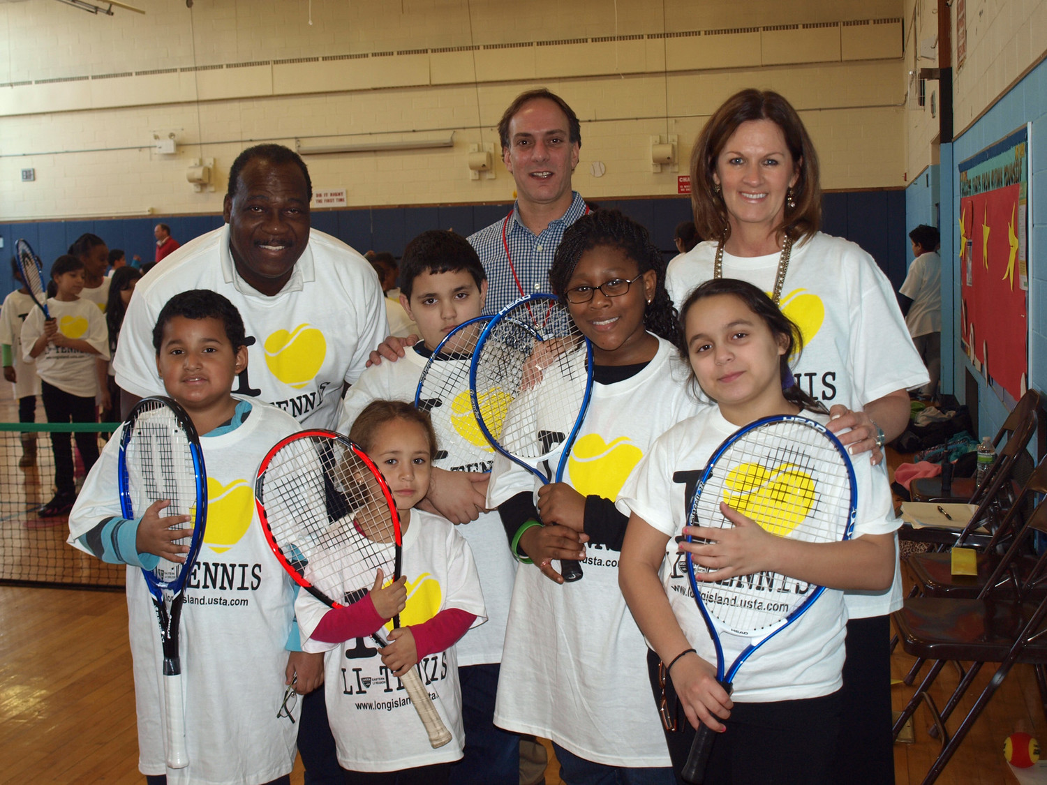 Daniel Burgess, standing at left, has taught hundreds of local children to play tennis.