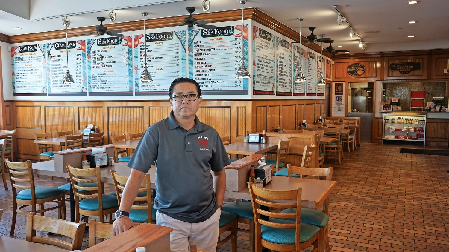 Peter's Clam Bar manager Pepe Poblador, left,  stood in the restaurant's empty dining hall on a warm day in September. Peter's owner Butch Yamali has criticized the county's handling of the bridge project, which he says has hurt business.