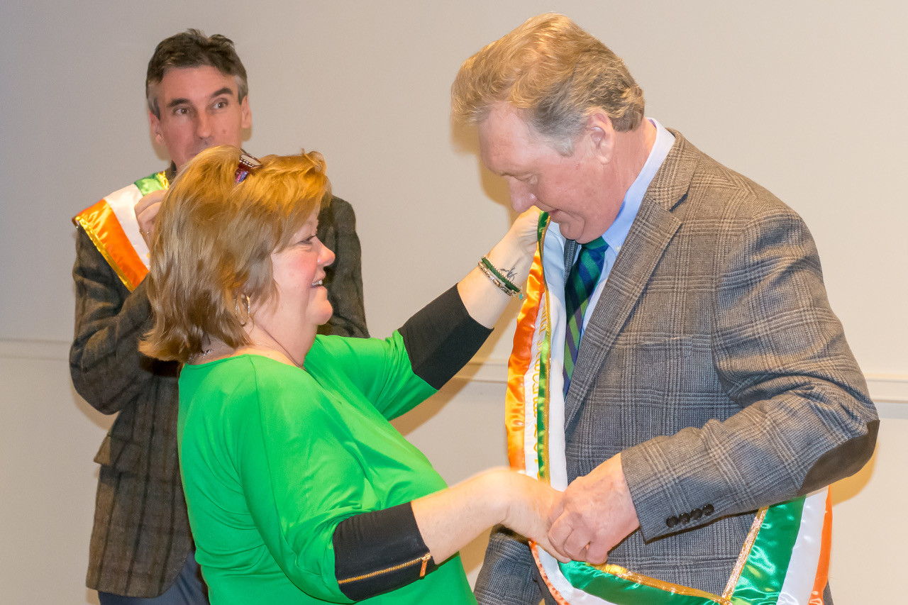 Lisa Bartley Forgione, of the Ladies Ancient Order of Hibernians, helped Grand Marshal Bill Doherty with his new sash.