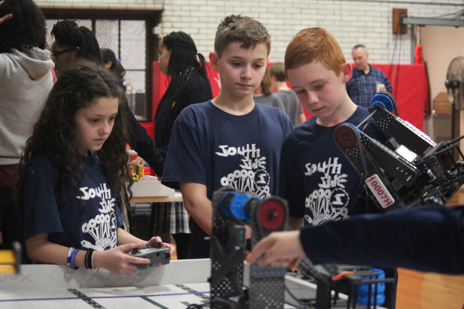 seventh-graders Melanie Koren, left, and Will Roesch prepped their robot for competition, as eighth-grader Kieran Cook looked on.
