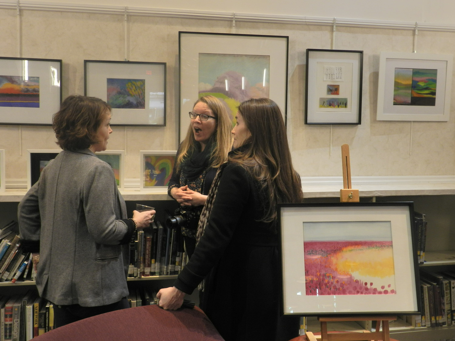 Sea Cliff Arts Council Co-chairwomen Kat DiResta, left, and Heidi Hunt, enjoyed the exhibit at the Sea Cliff Library with Miranda Best.