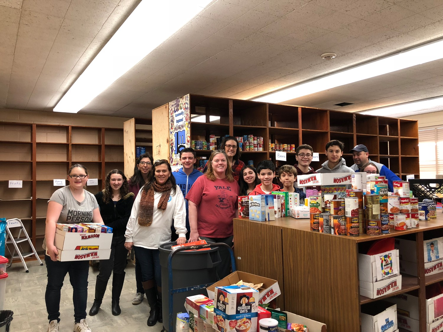 Community Cupboard organizers Karin McMahon, in scarf; Darlene Boden, in red T-shirt; and Catrina Christensen, behind her, with student volunteers, recently collected donations for the Cupboard's expansion effort.