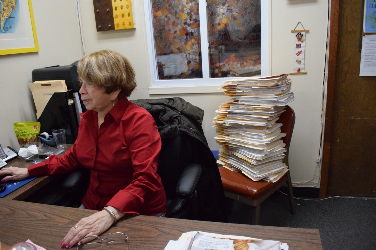 Mariann Mendoza, a volunteer receptionist and paralegal at the Central American Refugee Center in Hempstead, with a stack of TPS-related case files looming behind her.