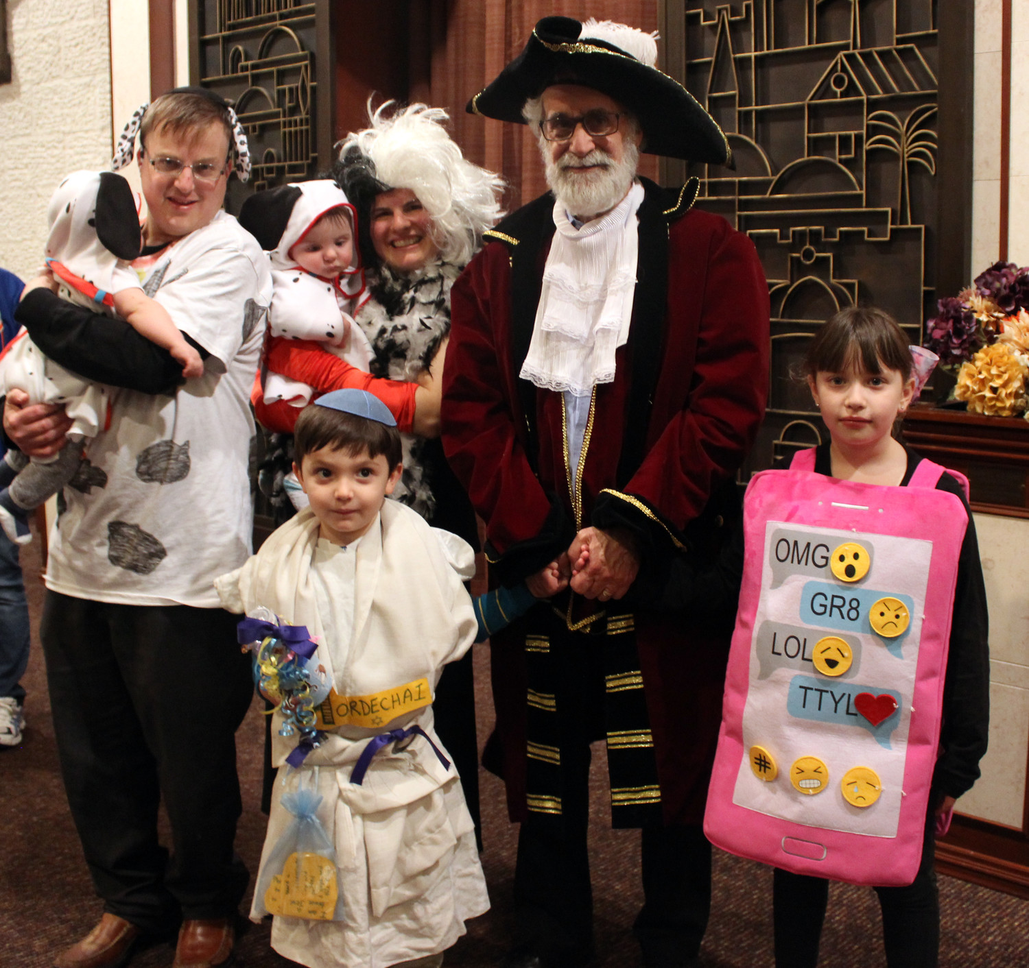 Rabbi Ronald Androphy awarded prizes to Howie Bank, center-left, his wife Stacy, and their nine-month old twin sons Samuel and Jack, all of whom dressed as Dalmatians, as well as Sky Schoenbereger, 4, who dressed as Mordechai and Adison Hurwitz, 7, who dressed as an I-Phone.