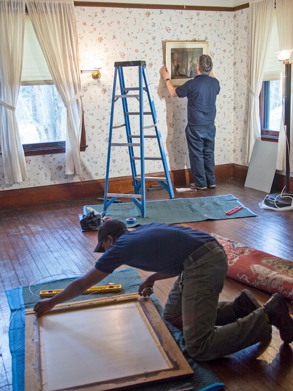 "workers from U.S.ART rehng painting in ""Big Guest Room"" rehanging art work on exact locations from which they were removed."