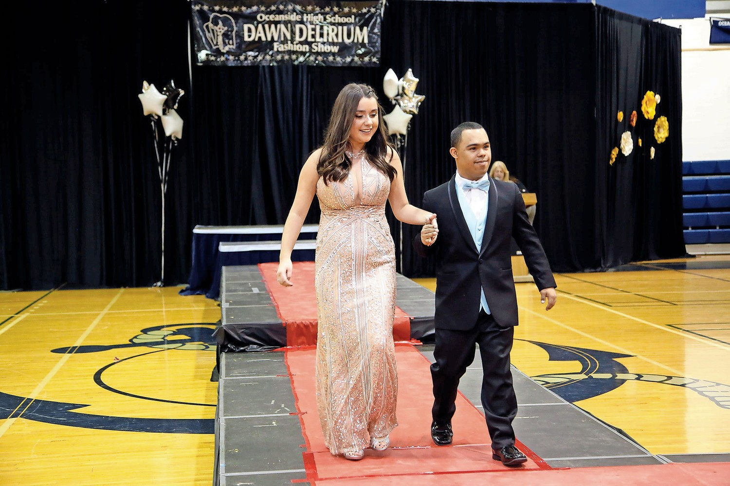 Benny Reyes leads Shona Daly off the red carpet after modeling their fancy garments.