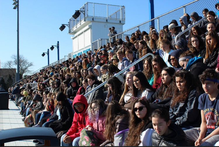 About 400 students, rallied by junior Madison Gusler, sat in the football field bleachers for 17 minutes in silence on Wednesday to honor the 17 victims of the Parkland, Fla., shooting.