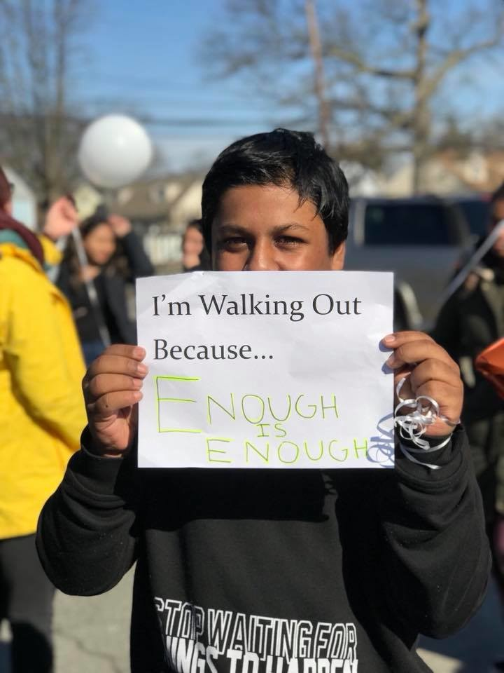 Aman Islam held up a sign at Central High School's walkout.