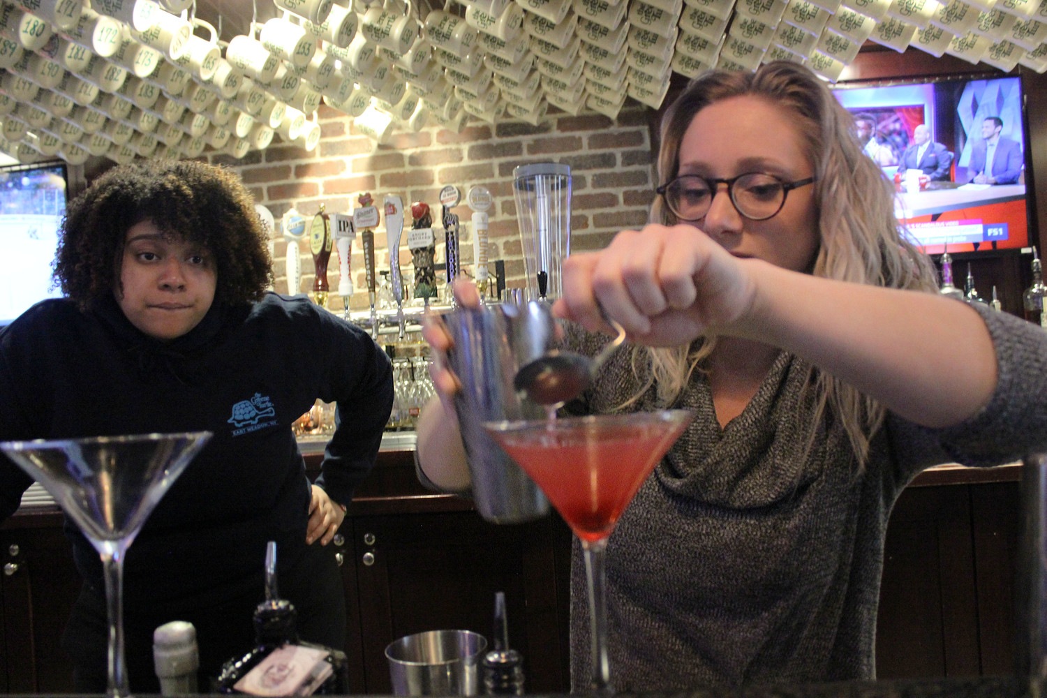 De Los Santos, left, and Baumann created an elegant twist on the classic cosmopolitan. Baumann is pictured delicately pouring the rest of the ingredients over a layer of Chambord.