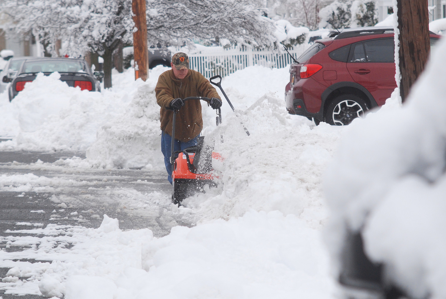 People across Nassau County spent Thursday morning clearing out their driveways after a nor'easter, which struck on the second day of spring, dumped nearly a foot of snow. Above, a resident of the Merrick Woods section of Merrick dug out in front of his home.