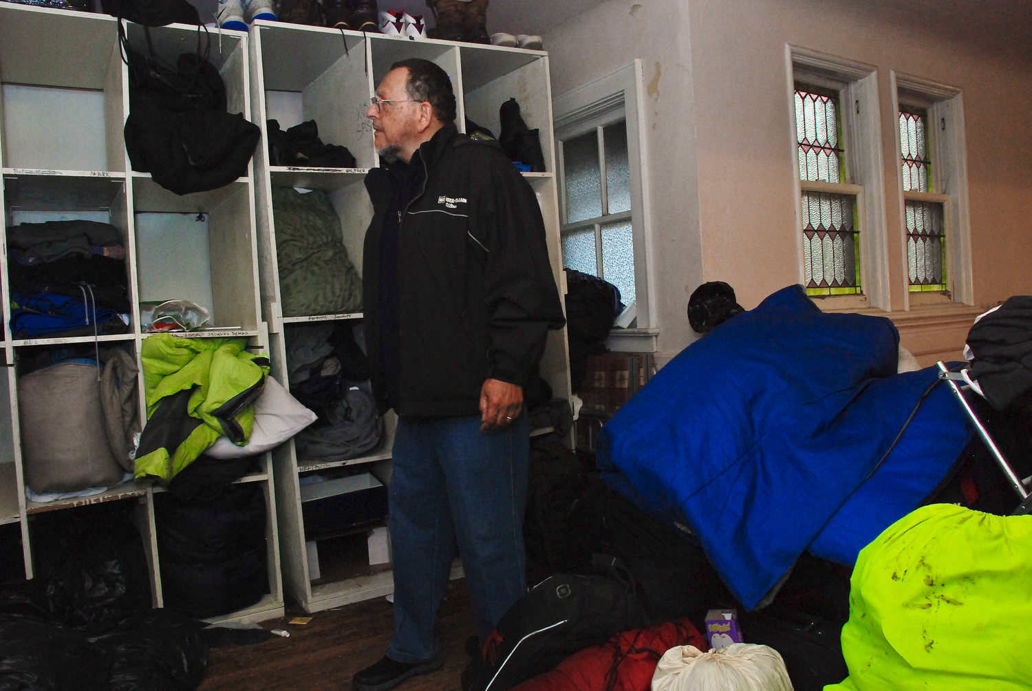 George, a member of the staff at the North Shore Sheltering Program, amid the cubbies where homeless men who spend their winter nights at the First Presbyterian Church keep their belongings during the day.