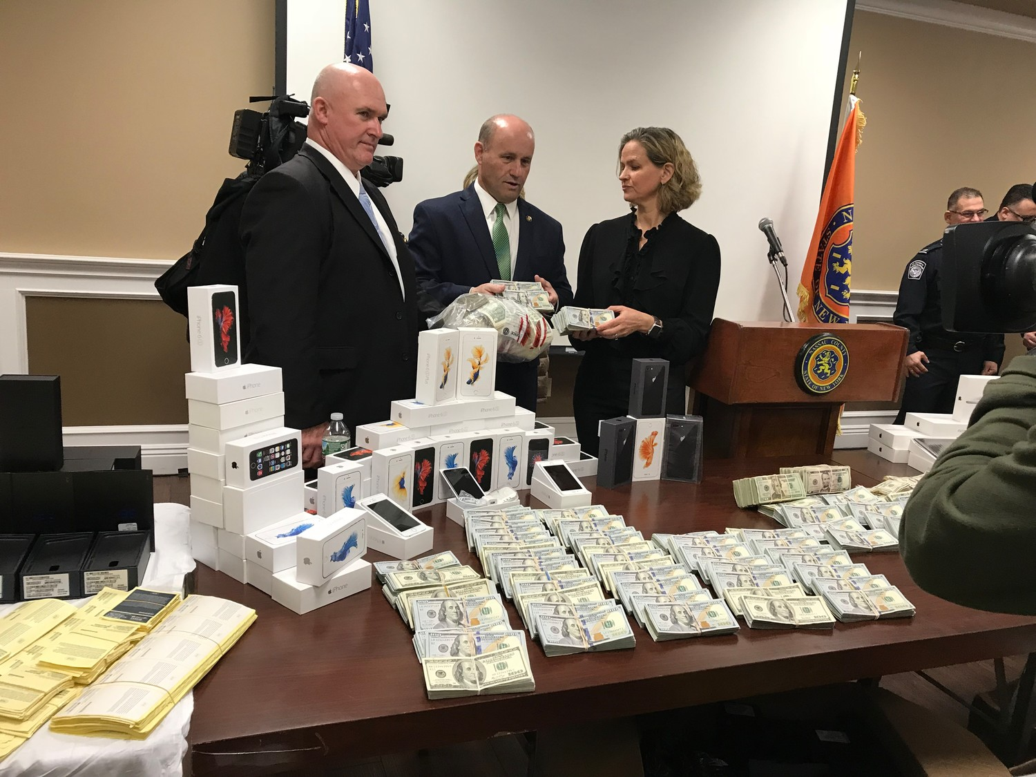 Nassau Police Commissioner Patrick Ryder, County Executive Laura Curran and Commanding Officer of the Asset Forfeiture Bureau Det. Lt. James Watson examine some of the $1.1 million in cash seized from the counterfeiting operation of the two Wantagh men who were arrested today.