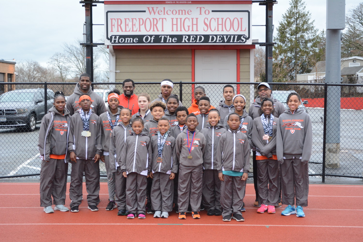 Athletes and coaches from the Explosion Track Club with their medals on the track at Freeport High School, where they practice.