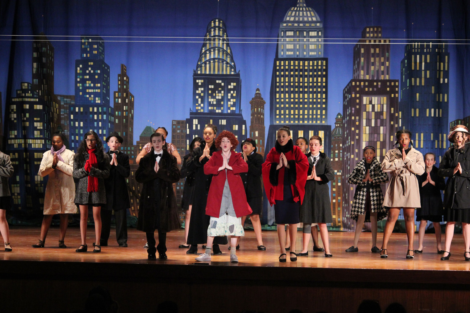"Set before a stunning backdrop, the cast sings the musical number ""N.Y.C."""