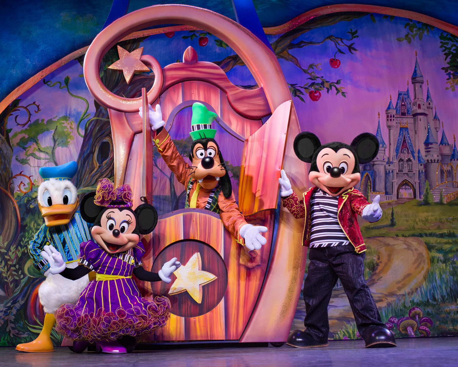 Mickey, Minnie, Goofy and Donald gather around a magic door.