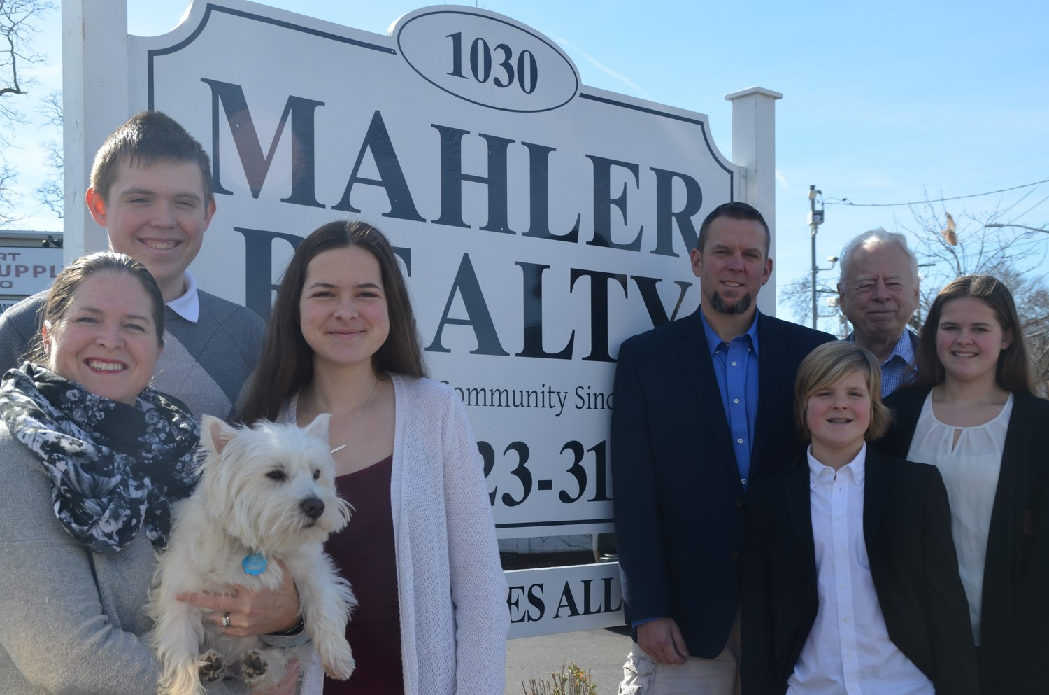 The Mahler family posed for a photo in from of the Mahler Realty sign. From left, Tracy holding Ben the dog, her kids Peyton, Karaline, Brady, and Kirsten, her husband Erik, and Rolf.
