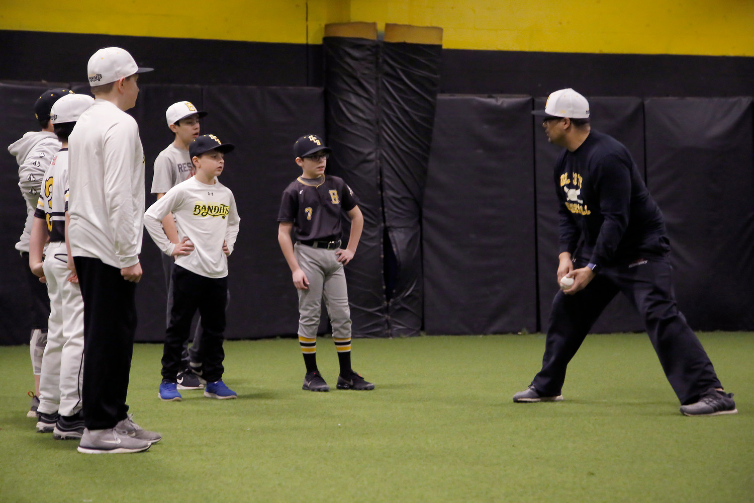 Coach Christian Paulino shows the 12-year old leaguers the proper way of handling the infield.