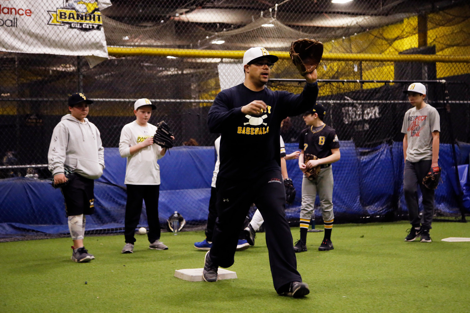 Coach Christian Paulino shows the 12-year old leaguers the proper way of catching in the infield.