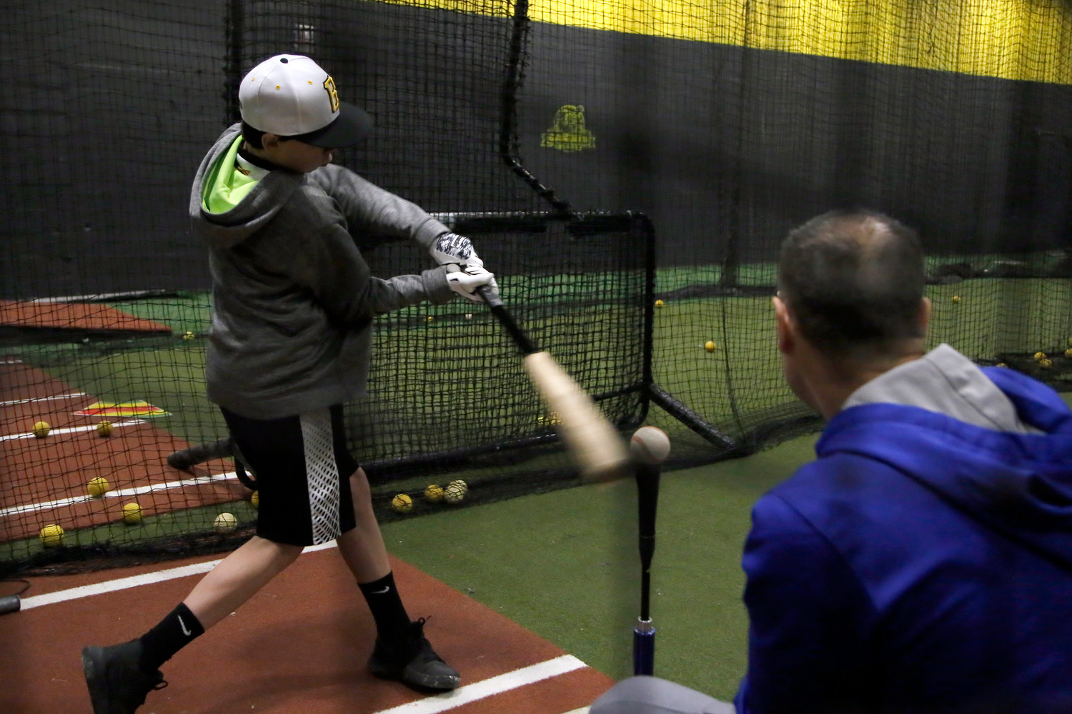 John Miedreich gives 13-year old Malverne resident Brendan Connolly some batting tips.