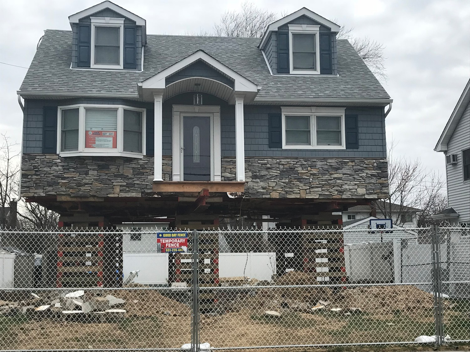 The Dalys' home in Wantagh was lifted but never set back down on a new foundation. They had to pay for the work-zone fence around it or risk hefty Town of Hempstead fines.
