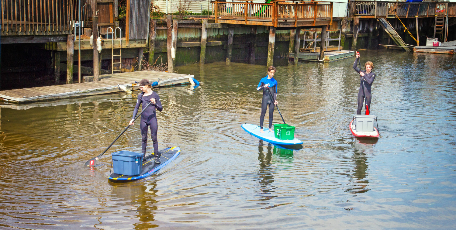 Volunteers Alexander Michelman, left, Rennie Leone and Jack Rockefeller used paddleboards to collect floating debris during the Surfrider canal cleanup in April 2015.