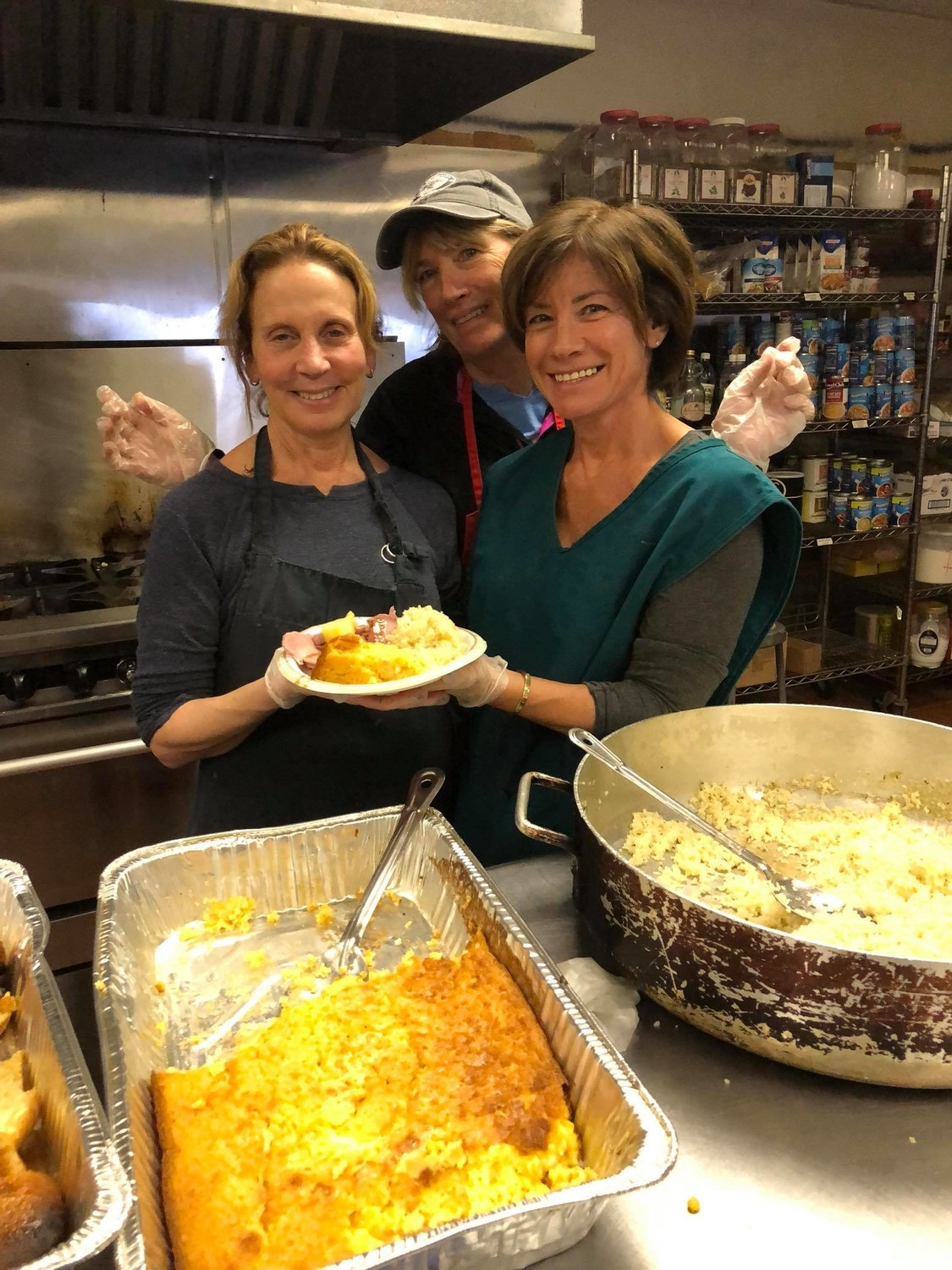 Volunteers Susan Kraetz Deutsch, left, Eileen Doherty Heneghan and Linda Bono MacDonald served ham, corn soufflé and rice to guests at the Long Beach Soup Kitchen on Feb. 9.