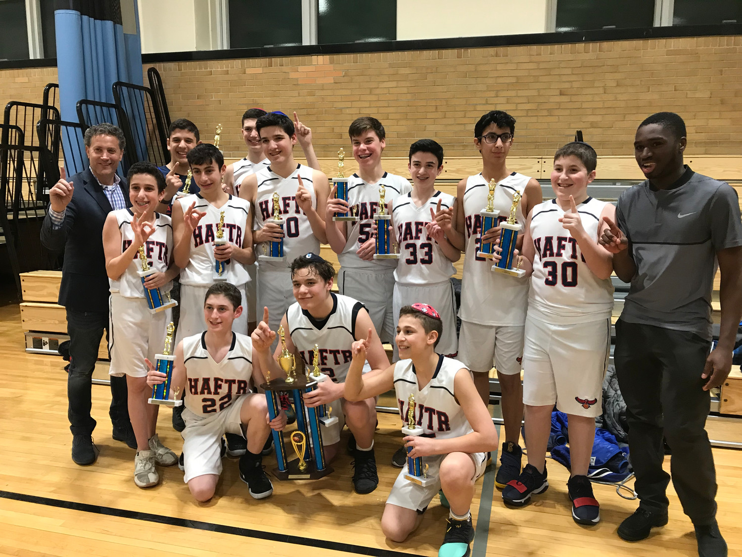Both HAFTR Hawks hoops team claimed league titles this season. The boys squad with coaches Joey Hoenig at the far left and assistant Joel Samuel at the far right.