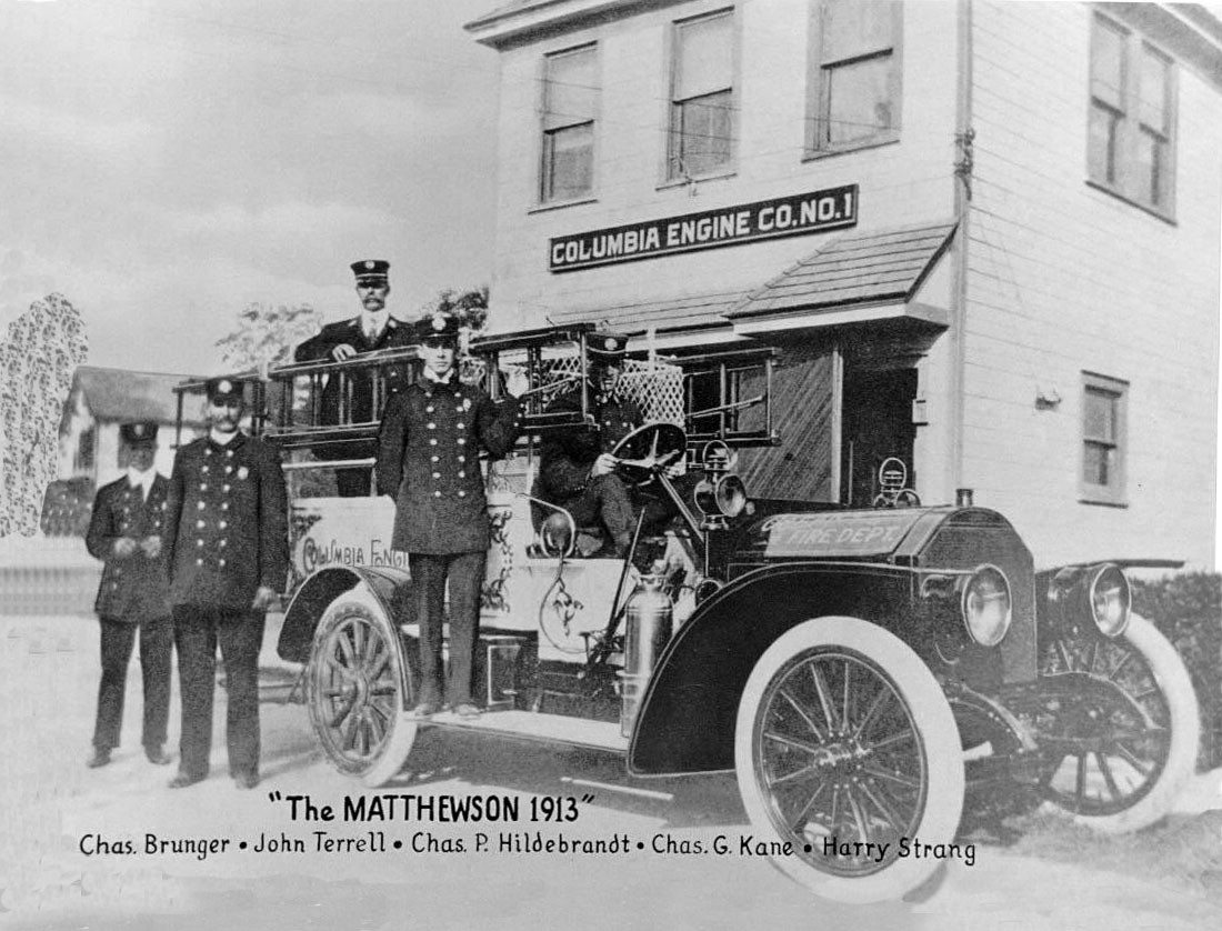 Members of Columbia Engine Company No. 1 in front of the Matthewson fire engine, which was reportedly the first motorized fire apparatus on Long Island. The firehouse behind them still stands today, at Lincoln and Davison avenues.