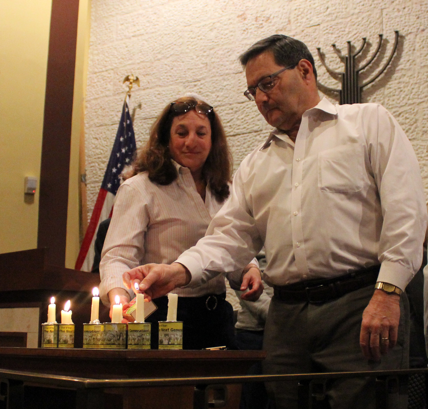 Holocaust survivors and their children lit candles to commemorate the six billion Jewish lives los. Pictured are Heide Mermelstein Landau and Frank Berkowitz.