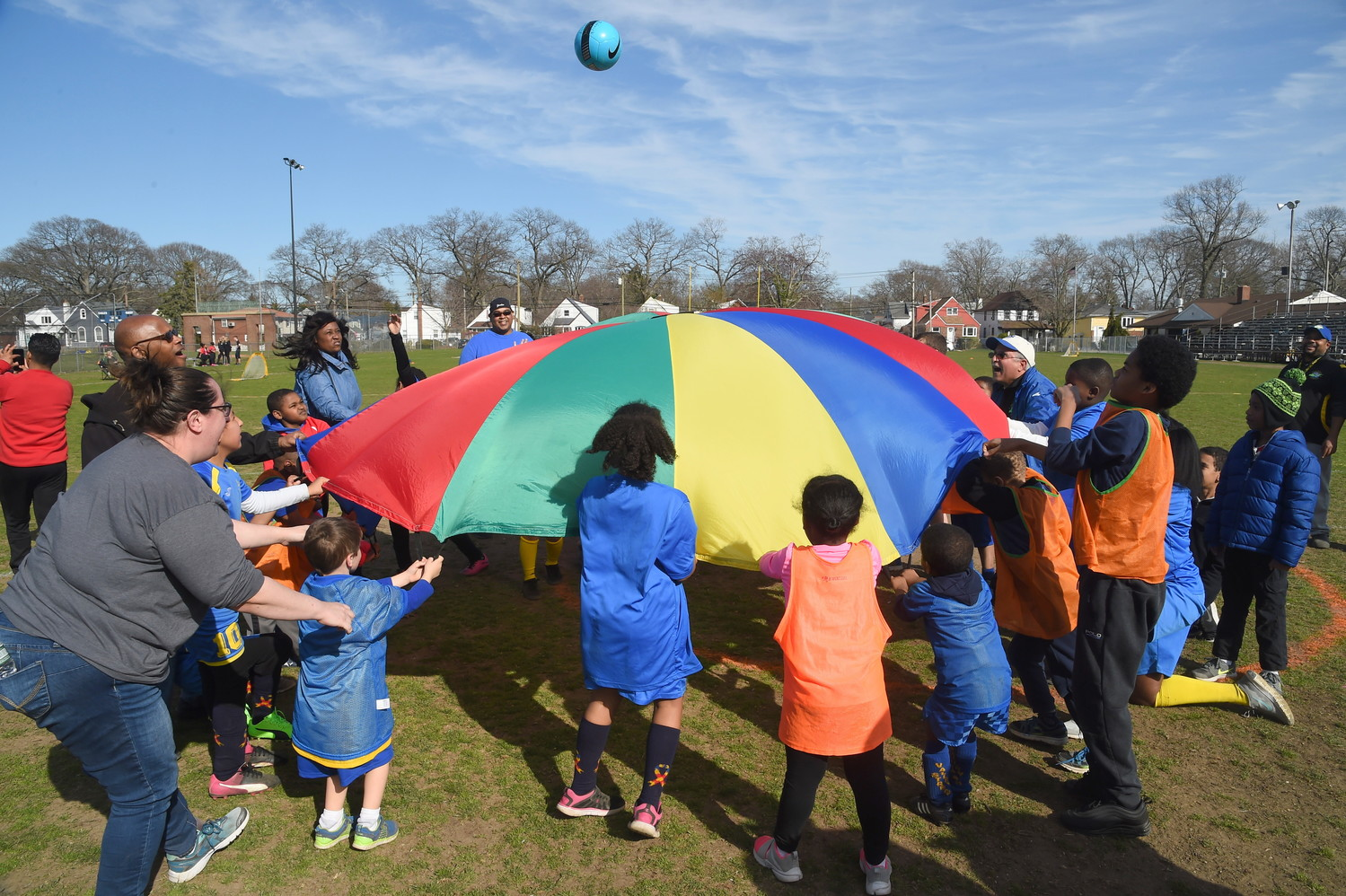 Children and parents used a brightly colored parachute to toss a soccer ball.