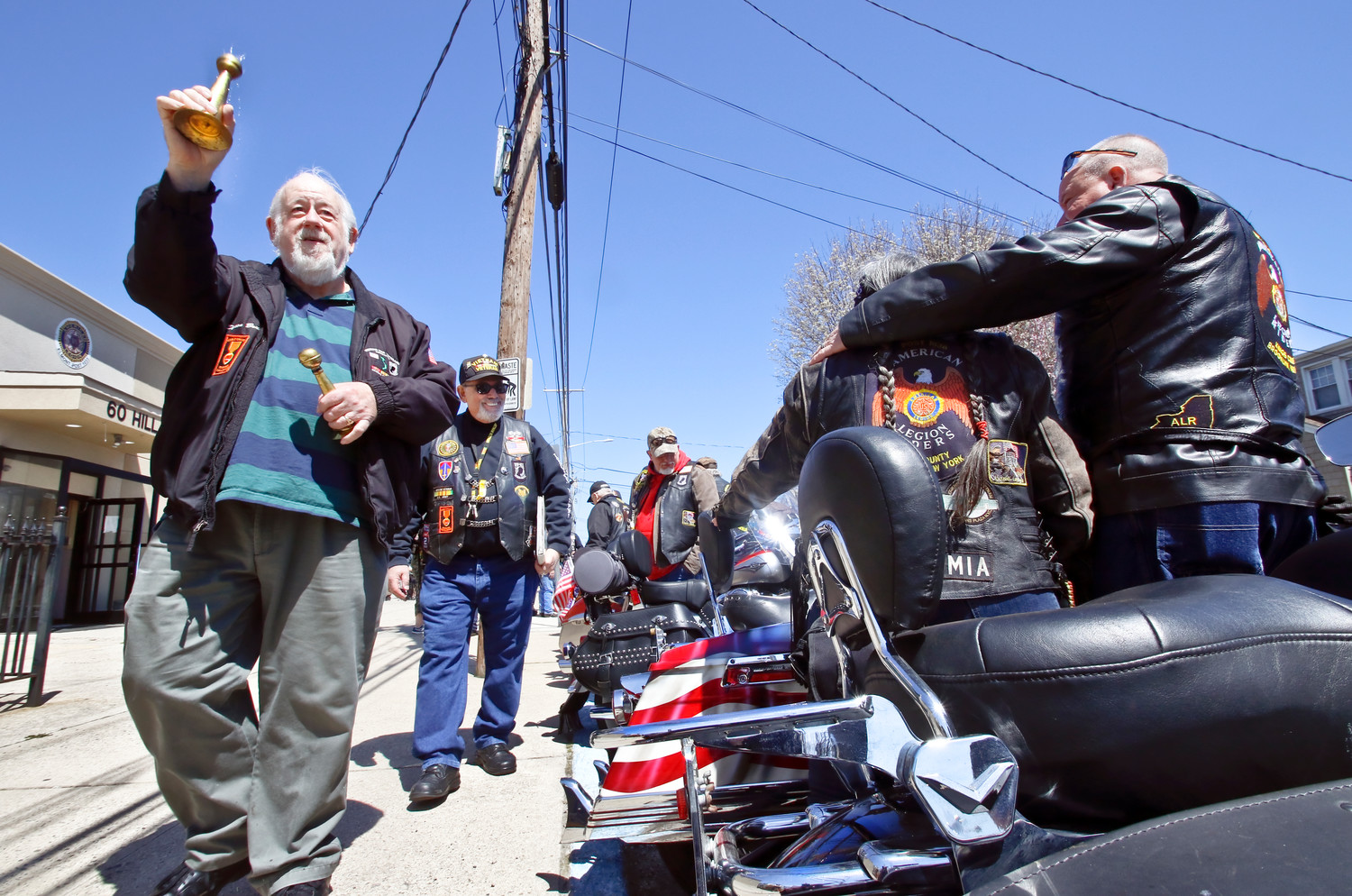 During the annual Blessing of the Bikes at the Elmont American Legion, Deacon Bruce Burnham, from Holy Redeemer Church in Freeport, sprinkles holy water on each motorcycle after reciting the Motorcyclists's Prayer. He is followed by Sal Martella, founder of the Elmont Legion Riders.