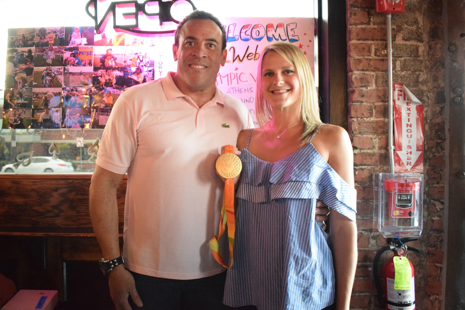 U.S. Paralympian Lora Webster showed off her gold medal to Franklin Square's Lucky Bar 13 owner Gregory Cajuste.