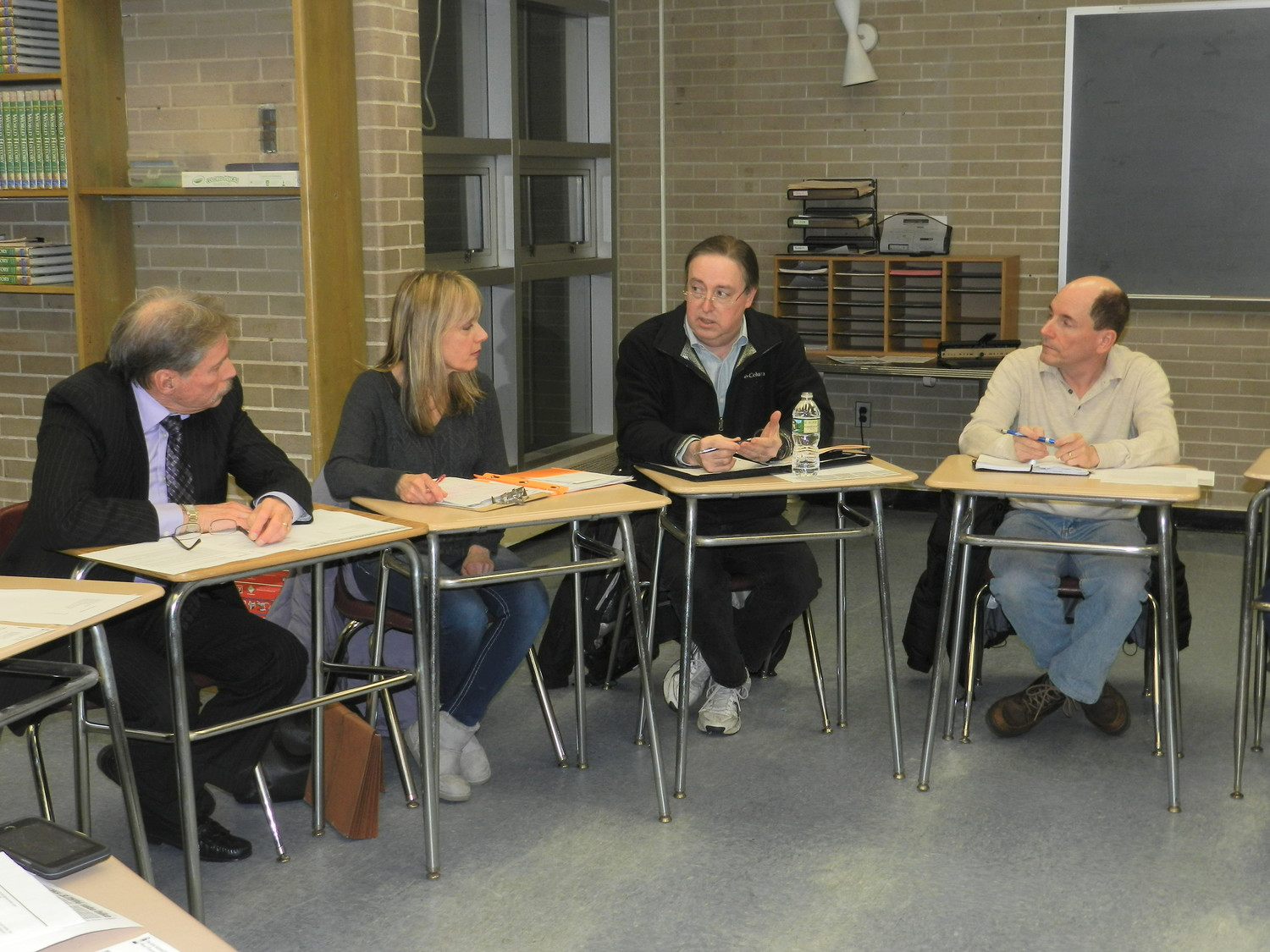 Residents Lloyd and Agatha Nadel, left, Joe Lopes and Steve Warshaw discussed the group's plans to oust New York American Water from the area at a North Shore Concerned Citizens meeting on April 17.
