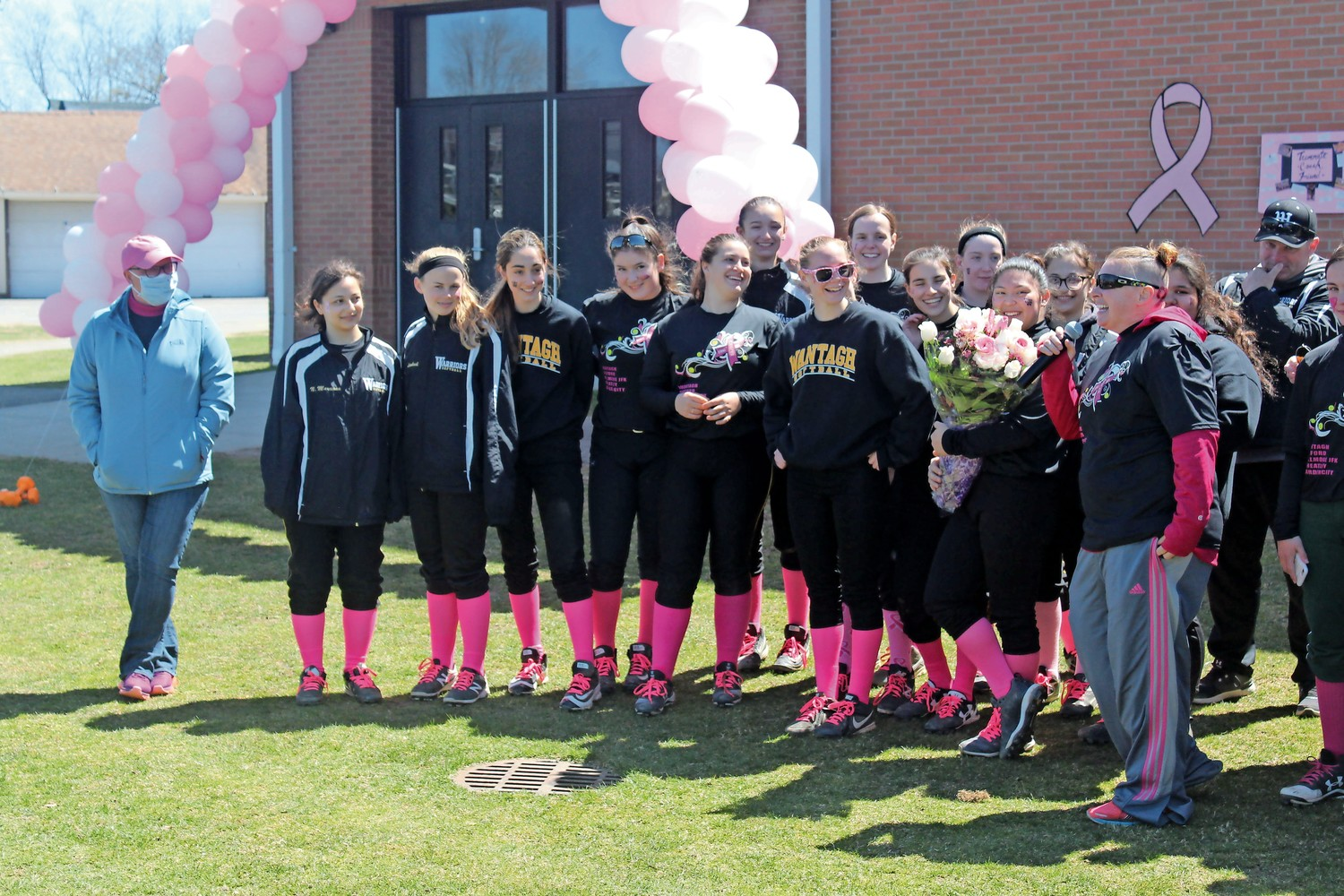 Butler, far left, received a bouquet of flowers from, and was the focus of a speech by, Wantagh head softball coach Christine Moran.
