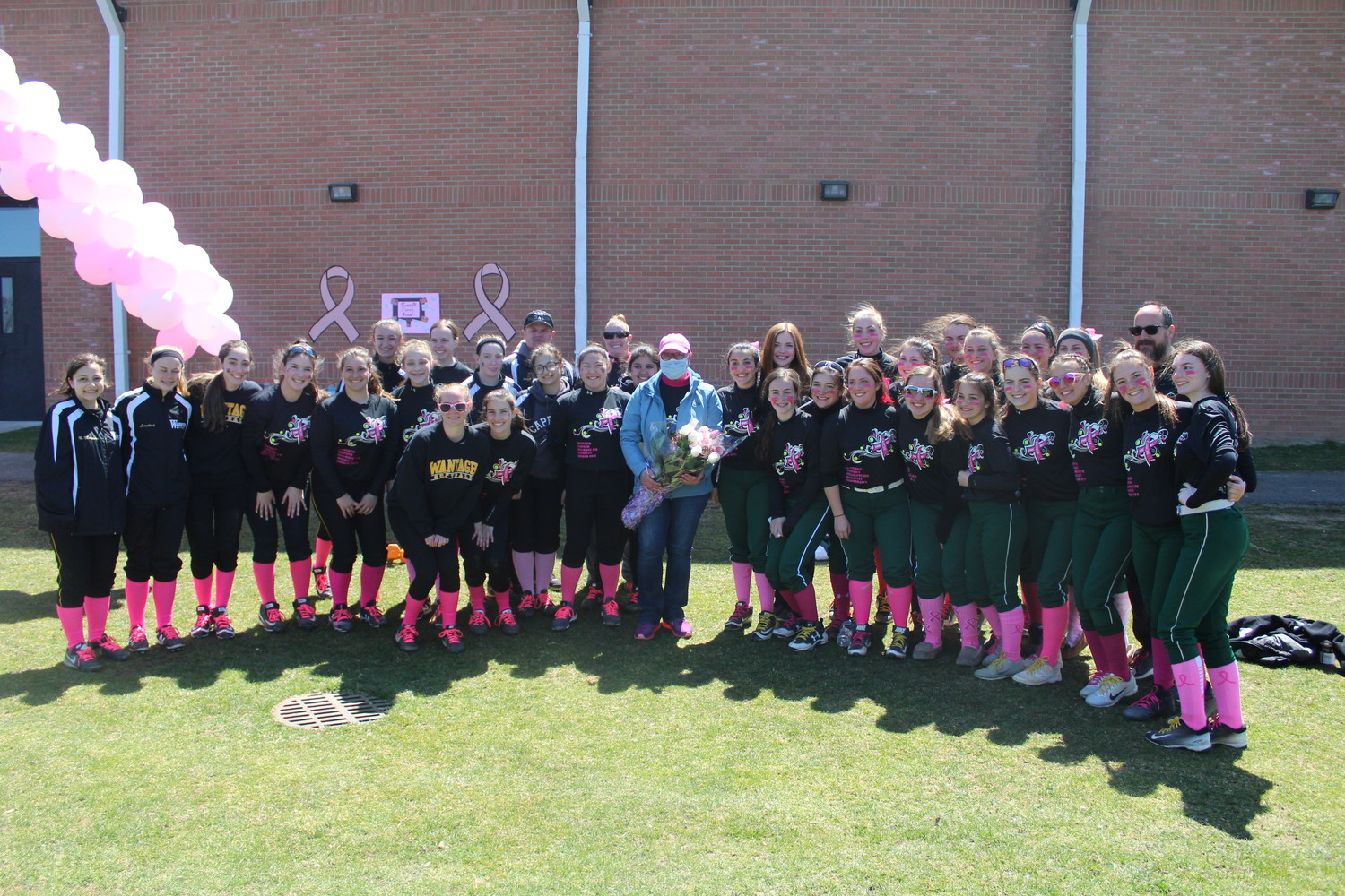 The Wantagh and Seaford High School softball teams joined forces to raise money for breast cancer in honor of local softball legend Kathy DelGais Butler, center.