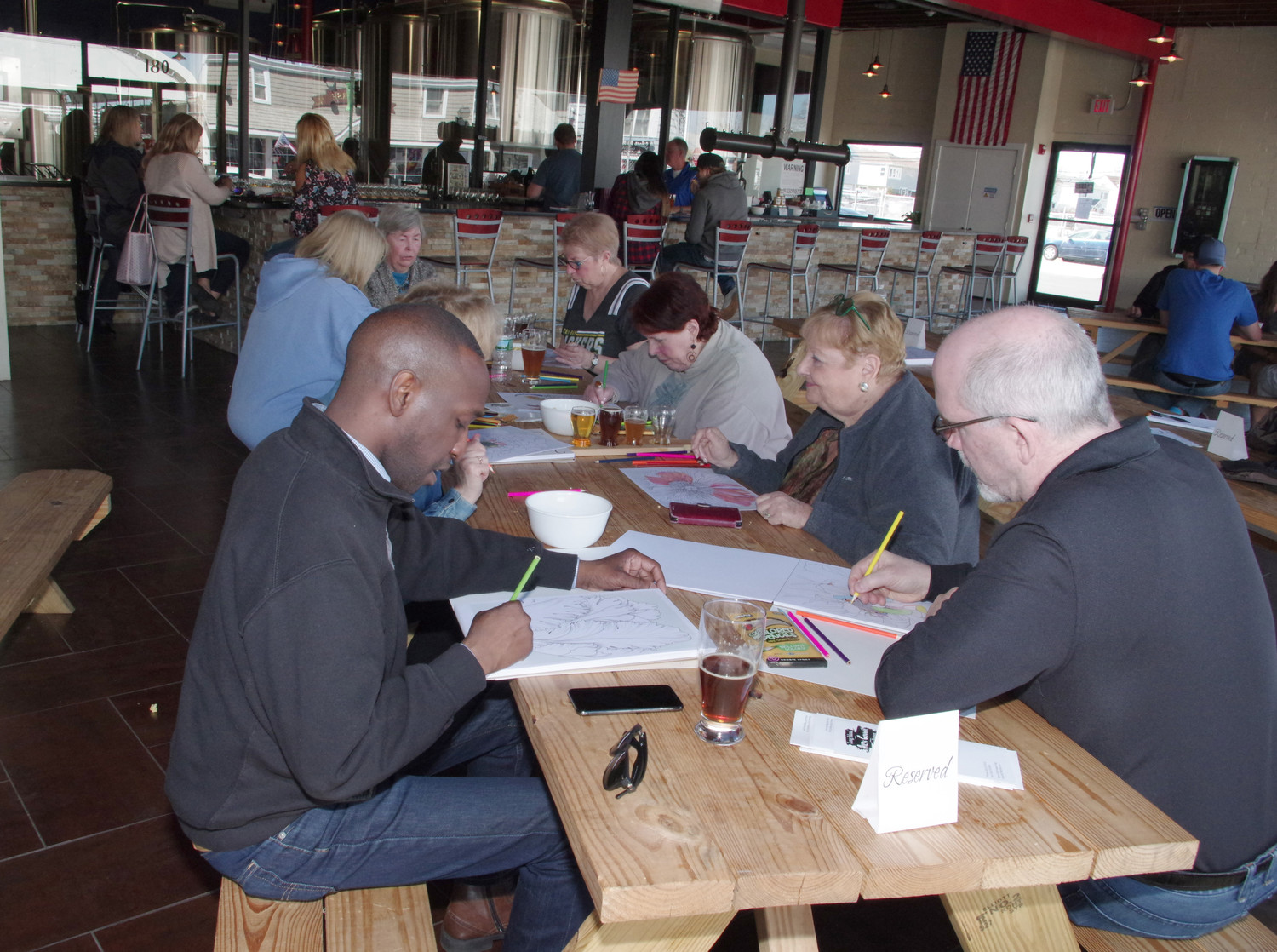 Long Island Arts Council board members colored and drank at BrewSa Brewery during a fundraiser held on Sunday.