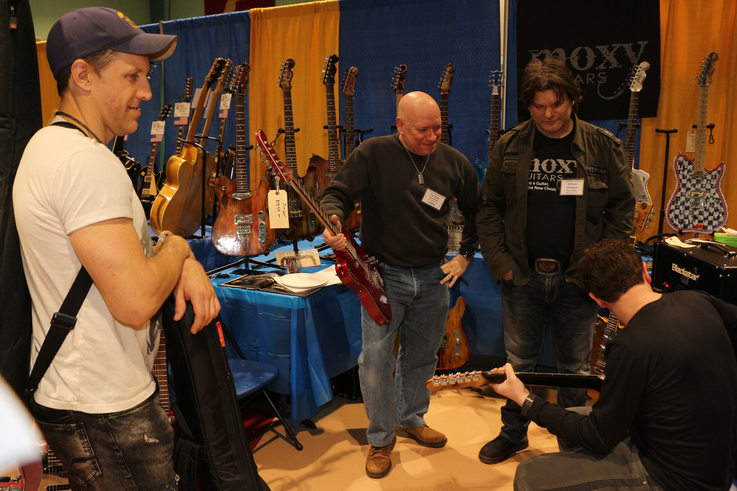 Scott Fisher, left and Michael Lisante expressed their interest in Jose Suros and Anthony Gemignani's, right, Moxy Guitars — custom worn and relic styled guitars.