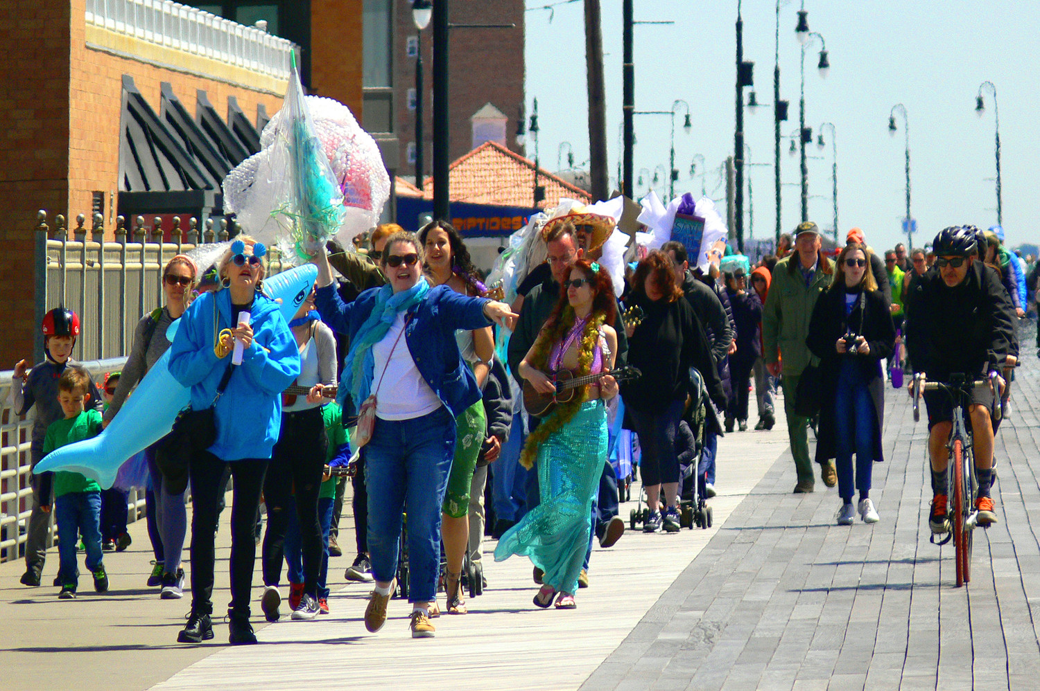 Johanna Mathieson, executive director of Artists in Partnership, far left, and Elizabeth Connolly, director of development for the LBNY-Arts Council, led an energetic parade along the boardwalk last Sunday at the Jellyfish Jamboree Earth Day celebration.