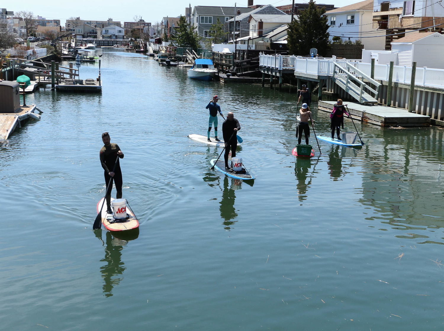 Volunteers stood on stand up paddleboards as they collected debris in buckets.