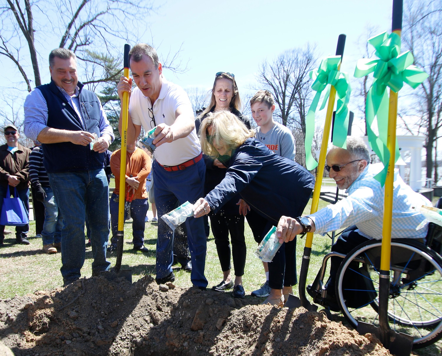 """We're politicians — we're all full of fertilizer!"" U.S. Rep. Tom Suozzi, second from left, joked as he, Mayor Tim Tenke, far left, and council members Pamela Panzenbeck and Michael Zangari sprinkled tree food into the hole where the sapling would soon be planted. Suozzi's wife, Helene, and son Michael watched from behind."