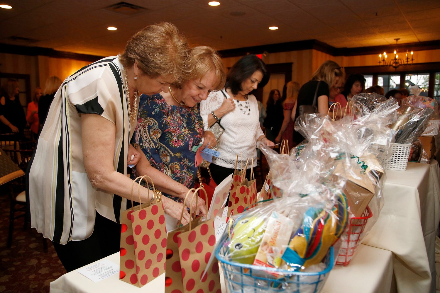 Marilyn Martin, left, Marion Locascio and Janet Schoenemann browsed through baskets to check out the raffle prizes.