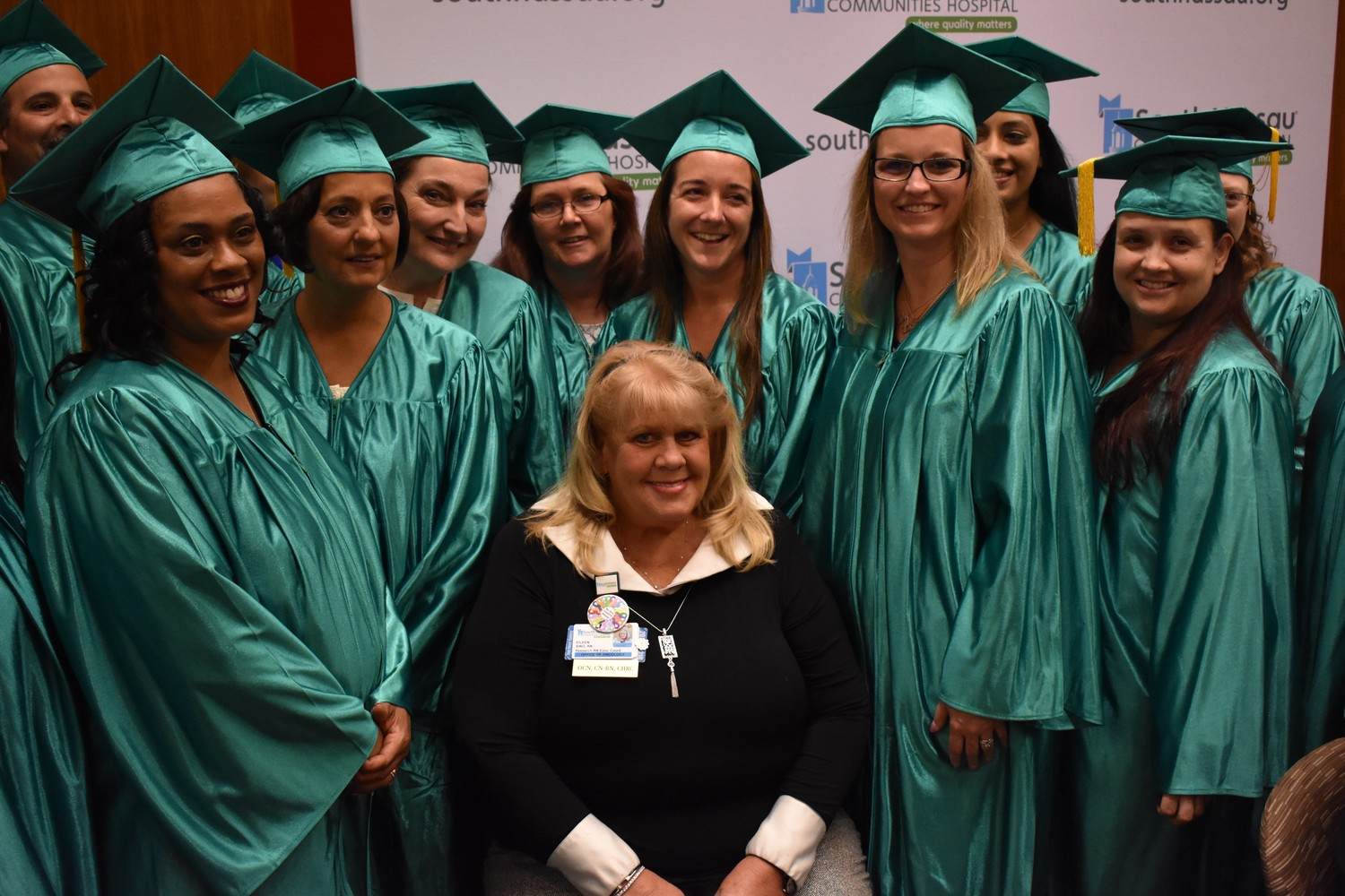 Rockville Centre resident Eileen Sino, center, who has worked with oncology patients at South Nassau Communities Hospital for 25 years, sat among nursing school graduates during a Nurses Day Celebration on May 4 after being named the hospital's Nurse of Excellence Award recipient.