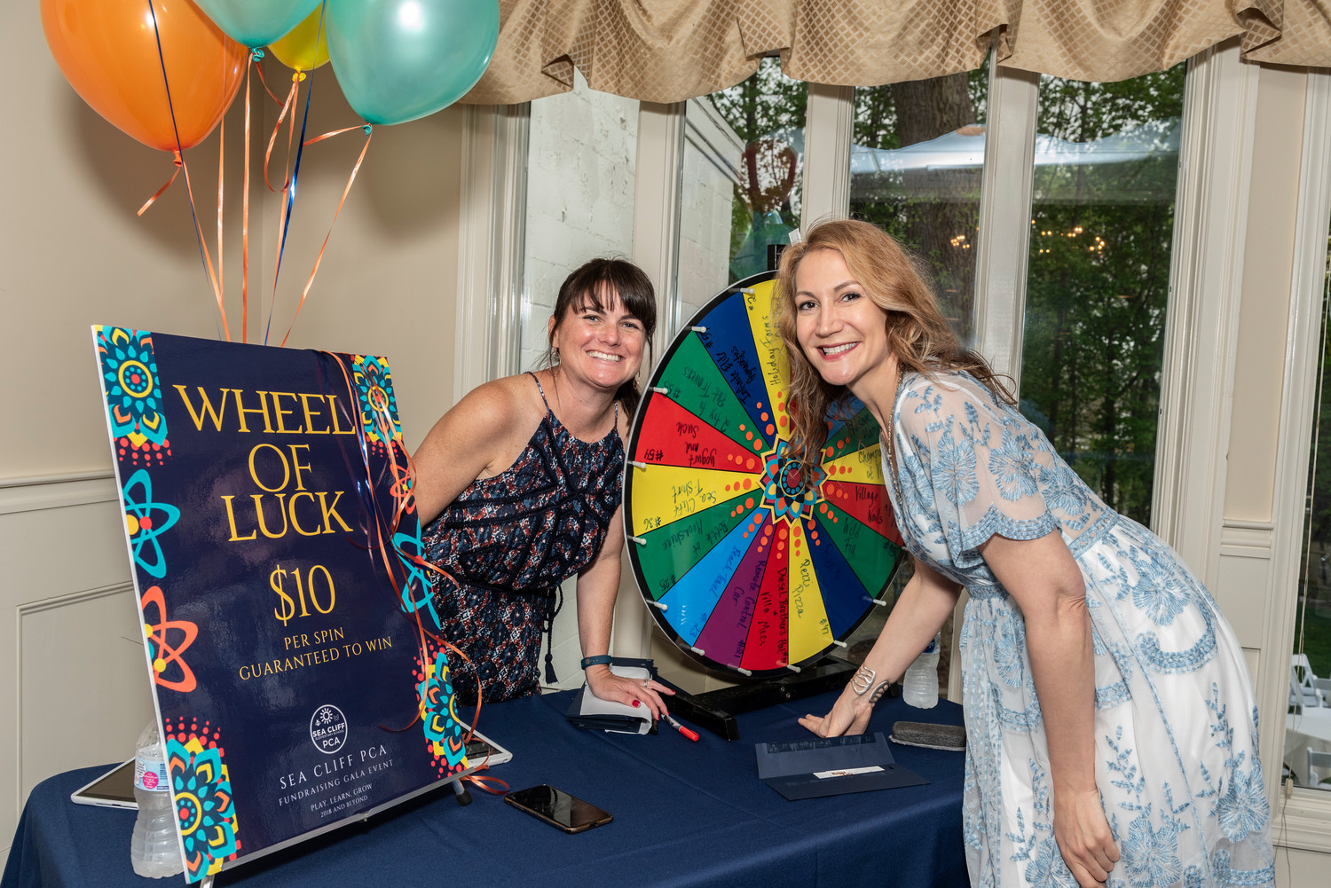 Laura Ryniker, left, and Heidi Hess worked the prize wheel during the event.