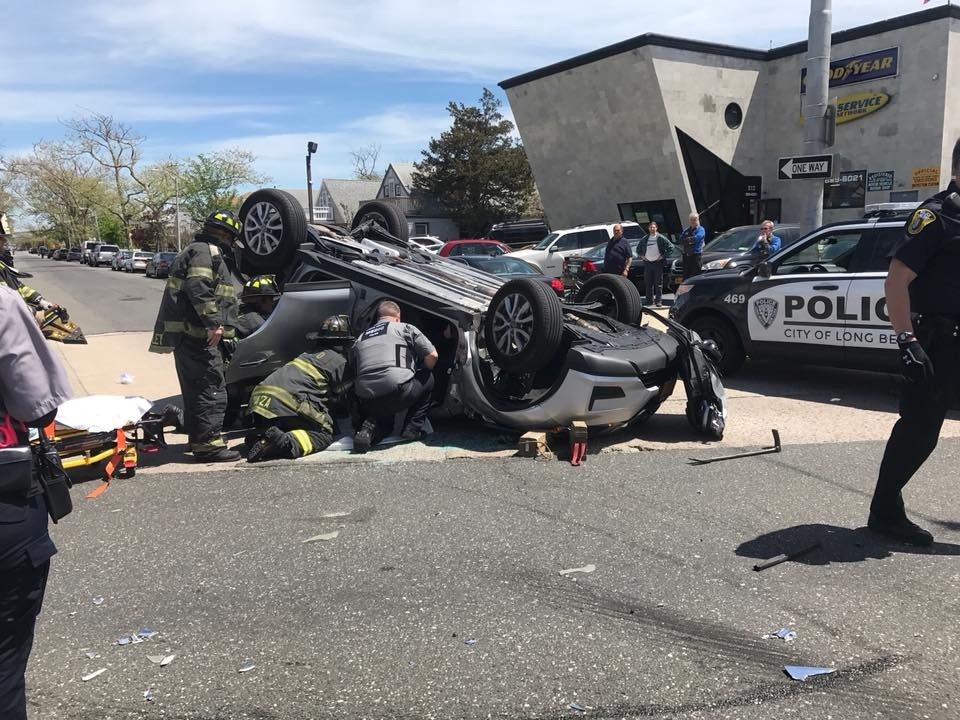Long Beach firefighters and police rushed to the scene of a two-car collision on Friday which left a woman pinned in an overturned car.